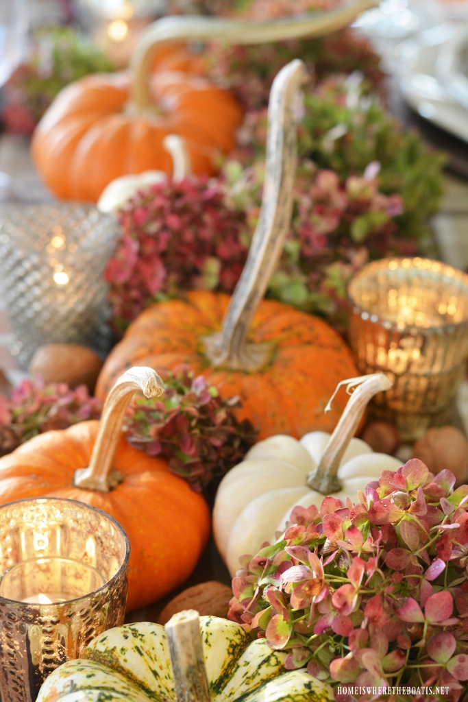 Fall table with an organic centerpiece table runner with pumpkins and hydrangeas | © homeiswheretheboatis.net #tablescape #fall #Thanksgiving