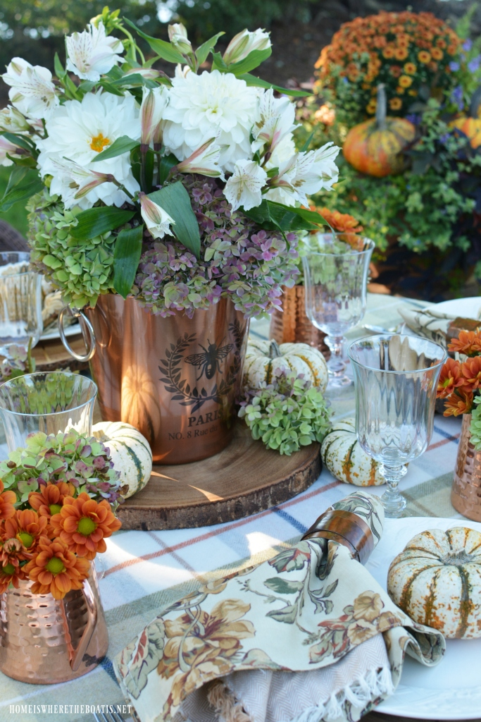 Fall alfresco tablesetting with copper wine bucket flower arrangement | ©homeiswheretheboatis.net #fall #alfresco #lake #flowers #hydrangeas #tablescapes #pumpkins