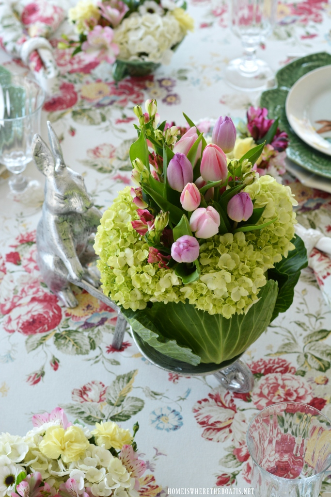 Bunny wheelbarrow with blooming cabbage flower arrangement and table centerpiece | ©homeiswheretheboatis.net #spring #tablescape #bunnies #easter