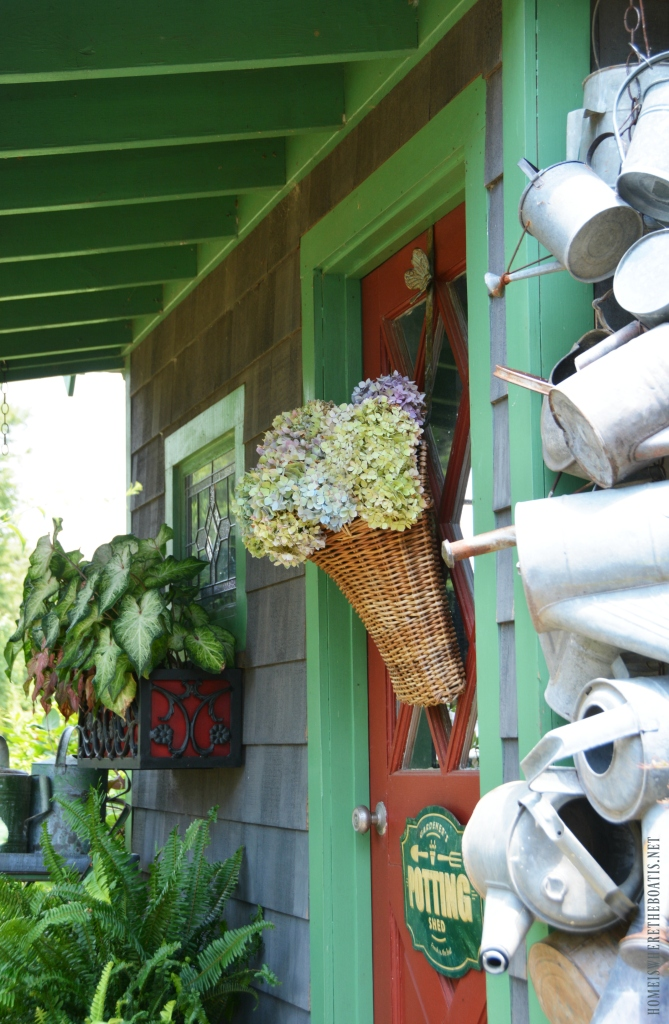 Hydrangeas in basket on Potting Shed door| ©homeiswheretheboatis.net #summer #garden #flowers #gardenshed #hydrangeas