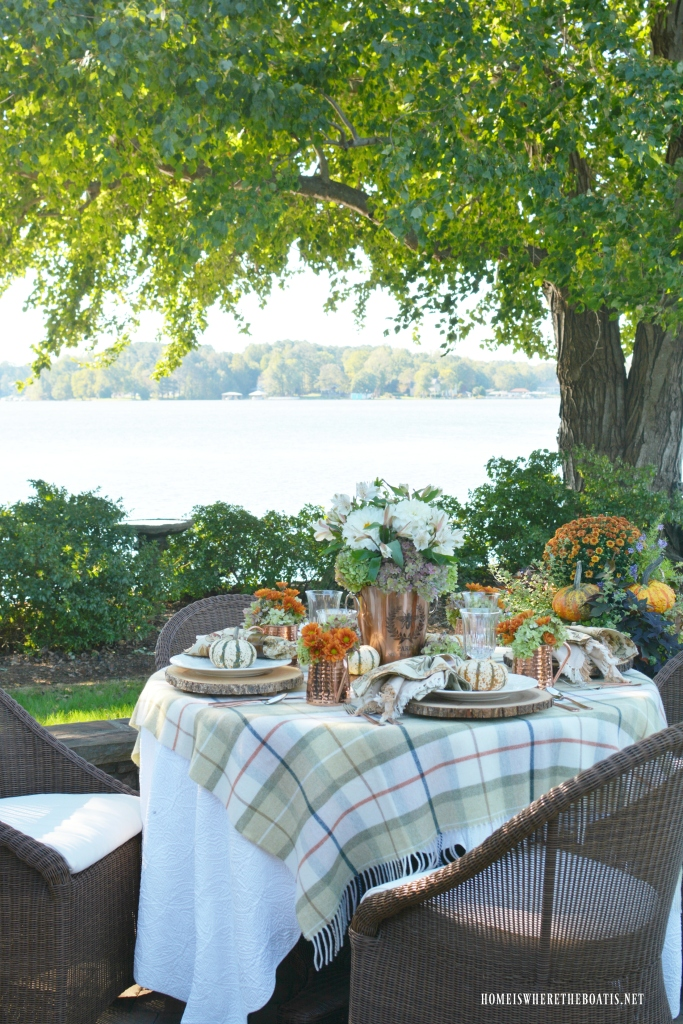 Fall alfresco tablesetting by lake with copper wine bucket flower arrangement | ©homeiswheretheboatis.net #fall #alfresco #lake #flowers #hydrangeas #tablescape #pumpkins