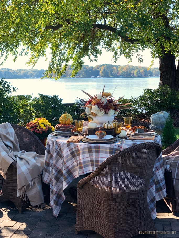 Fall tablescape and flower arrangement with feathers | ©homeiswheretheboatis.net #fall #tablescape #alfresco #flowers #feathers