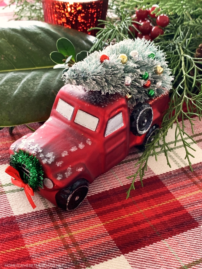 Red truck Christmas table with red truck ornaments | ©homeiswheretheboatis.net #christmas #truck #tablescapes #tartan #plaid