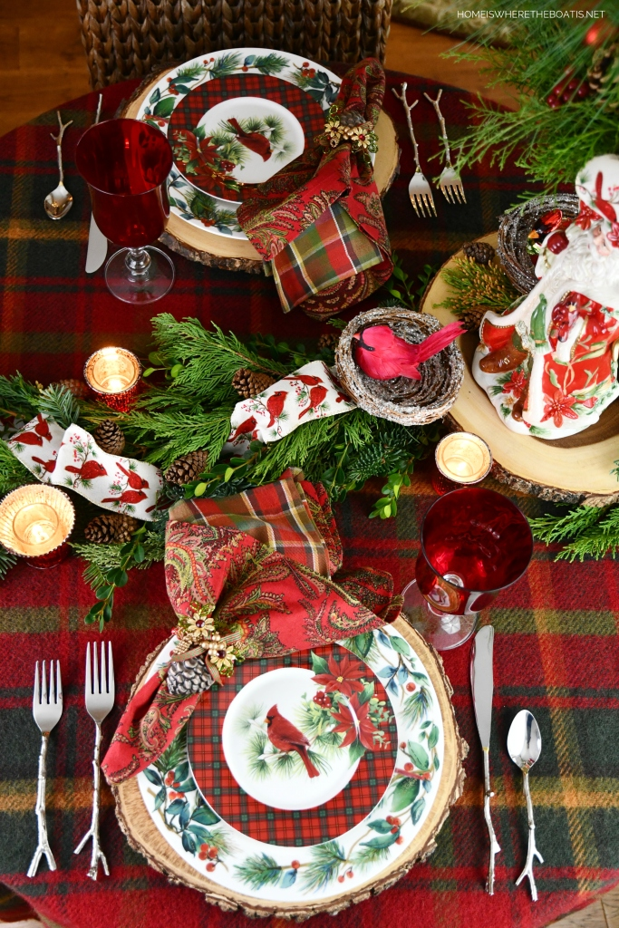 Cardinal Christmas tablescape with greenery, pine cones and Cardinal ribbon and ornaments | ©homeiswheretheboatis.net #Christmas #tablescapes #birds #tartan #plaid
