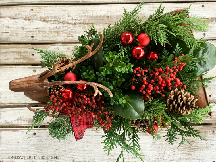 Deer sleigh centerpiece with fresh greenery, berries, ornaments, ribbon | ©homeiswheretheboatis.net