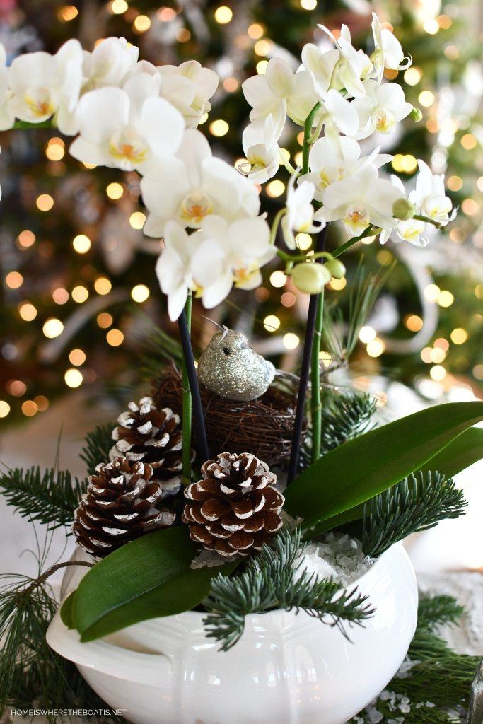 Bird ornament and nest in orchid arrangement