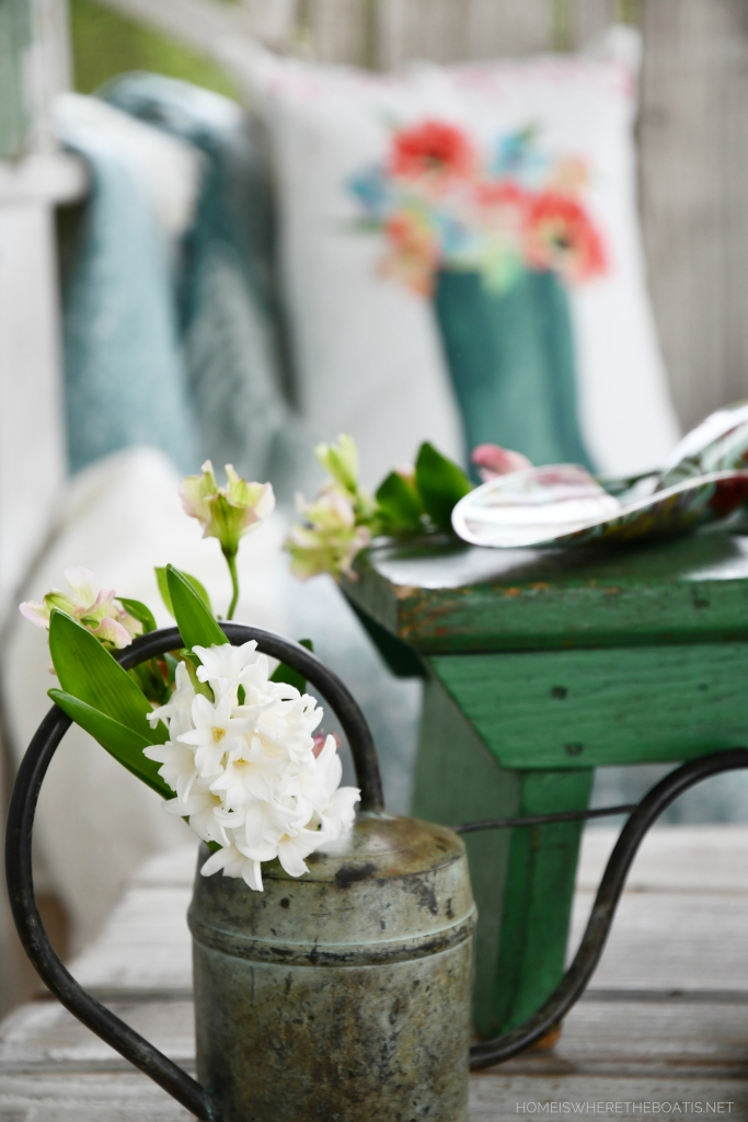 Spring on the porch and blooming watering can | ©homeiswheretheboatis.net #flowers #spring