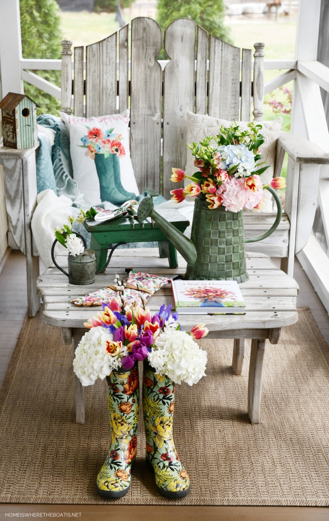 Spring on the porch with blooming wellies and watering can | ©homeiswheretheboatis.net #flowers #wellies #spring